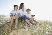 Familia sentada en la playa — Foto de Stock