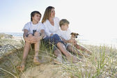 Family sitting on the beach — Stock Photo