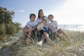 Familjen sitter på stranden — Stockfoto