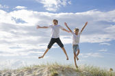 Boys jumping of a sand dune at the beach — Stock Photo