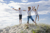 Mum and sons jumping of a sand dune at the beach — Stock fotografie