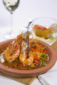 Sizzling prawns with condiments and wine — Stock Photo