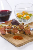 Beef served on skewers with condiments and red wine — Stock Photo