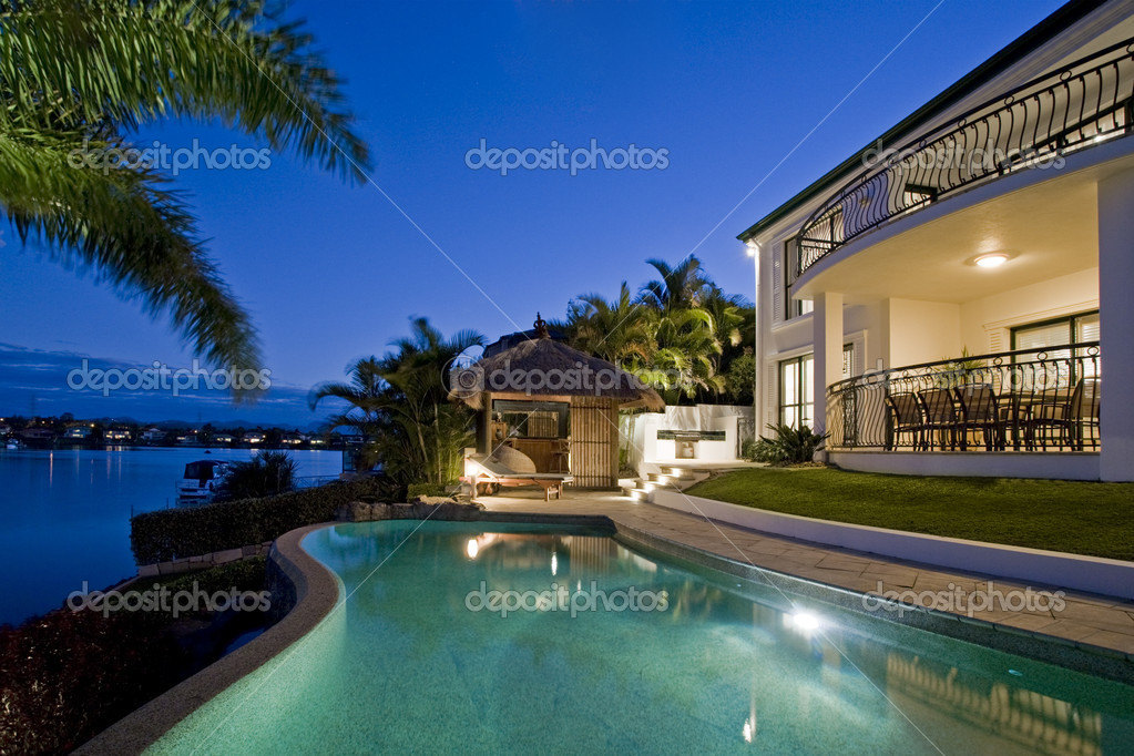 Luxurious mansion exterior at dusk overlooking pool, canal and Bali hut  Stock Photo #5785967