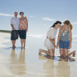 Sisters looking at shell on beach with parents in background — Stock Photo #5792059