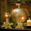Candles burning on table in front of old rustic door - Stock Photo