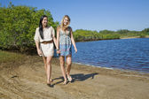 Two girls holding hands walking and giggeling by the creek — Stock Photo