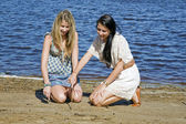 Two girls writning with stick in sand by the creek — Stock Photo