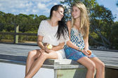Two girls eating apples by the creek on a sunny day — Stock Photo