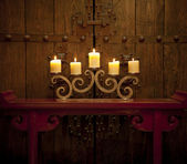 Candles burning on table in front of old rustic door — Stock Photo