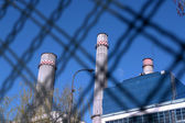 Power plant furnaces behind metal fence — Stock Photo