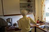 Senior in her kitchen — Stock Photo