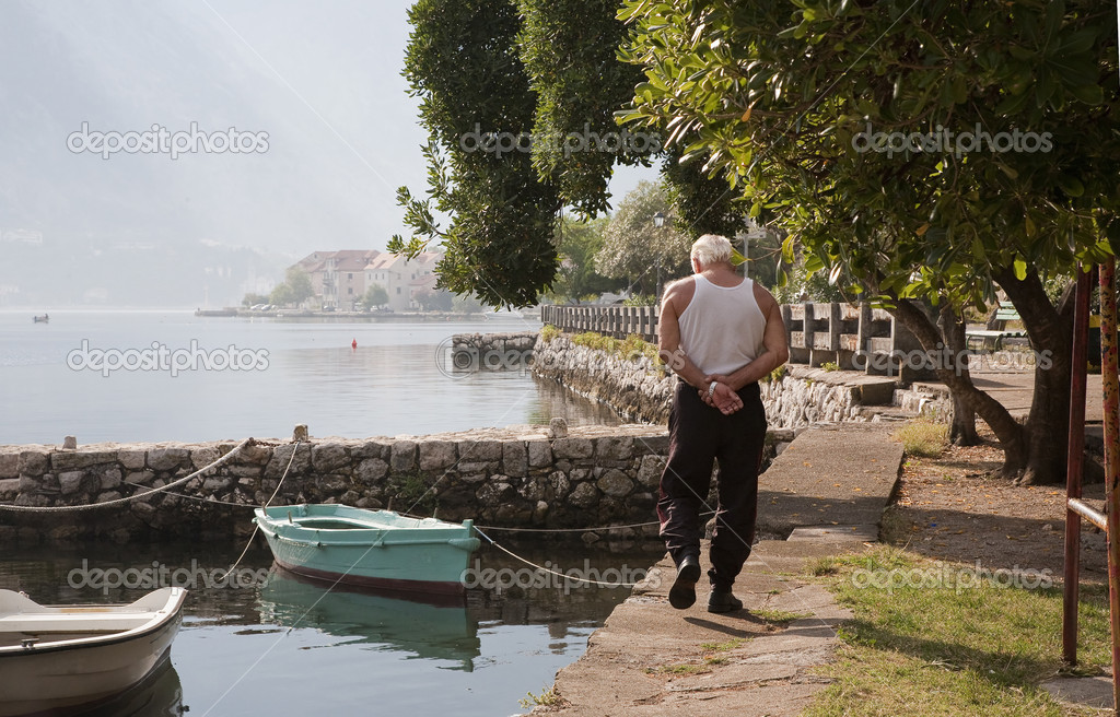 Fisherman walking along the coastline of Montenegro by the Adriatic Sea an early morning at summertime.  Stock Photo #6573956