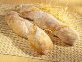 Freshly baked spicy baguette on table — Stock Photo