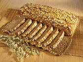 Freshly baked full grain bread and wheat on table — Stock Photo