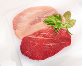 Raw pork chop and steak. Arrangement on a white cutting board. — Stock Photo