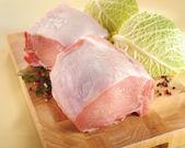 Raw pork roast with bone. Arrangement on a cutting board. — Stock Photo