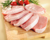Raw pork chops. Arrangement on a cutting board. — Stockfoto