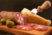 Salami with green olives and parmesan cheese — Stock Photo