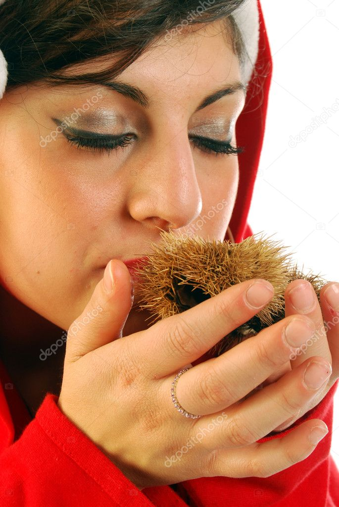 A woman dressed as Santa Claus smells the scent of chestnuts in their curly — Stock Photo #6740921