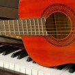 Acoustic guitar on piano keyboard — Stock Photo