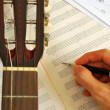 Guitar with hand composing music on manuscript — Stock Photo
