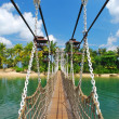 Wooden bridge leading to paradise island — Stock fotografie