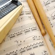 Music score, drum sticks and metronome — Stock Photo