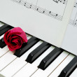 Red rose and music score on piano keyboard - Foto Stock