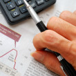 Closeup of writing hand and financial documents — Foto de Stock
