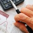 Closeup of writing hand and financial documents — Stockfoto