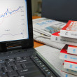 Financial books with graph on laptop — Stock Photo