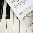 Writing on music score with pen on piano keyboard — Stock Photo