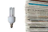 Light bulb and new newspapers — Stock Photo