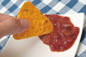 Dipping tortilla chip into sauce — Stock Photo