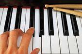Main gauche en jouant sur le clavier du piano avec baguettes — Photo