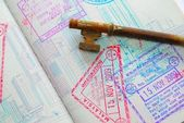 Key on passport full of stamps — Stock Photo