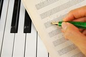 Writing on old music score with pen on piano keyboard — Stock Photo