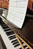 Musik poäng och trumma pinnar på piano keyboard — Stockfoto