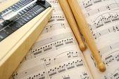 Music score, drum sticks and metronome — Stock Photo