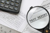 Closeup of magnifying glass on test report — Stock Photo