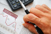 Closeup of writing hand and financial documents — Stock Photo