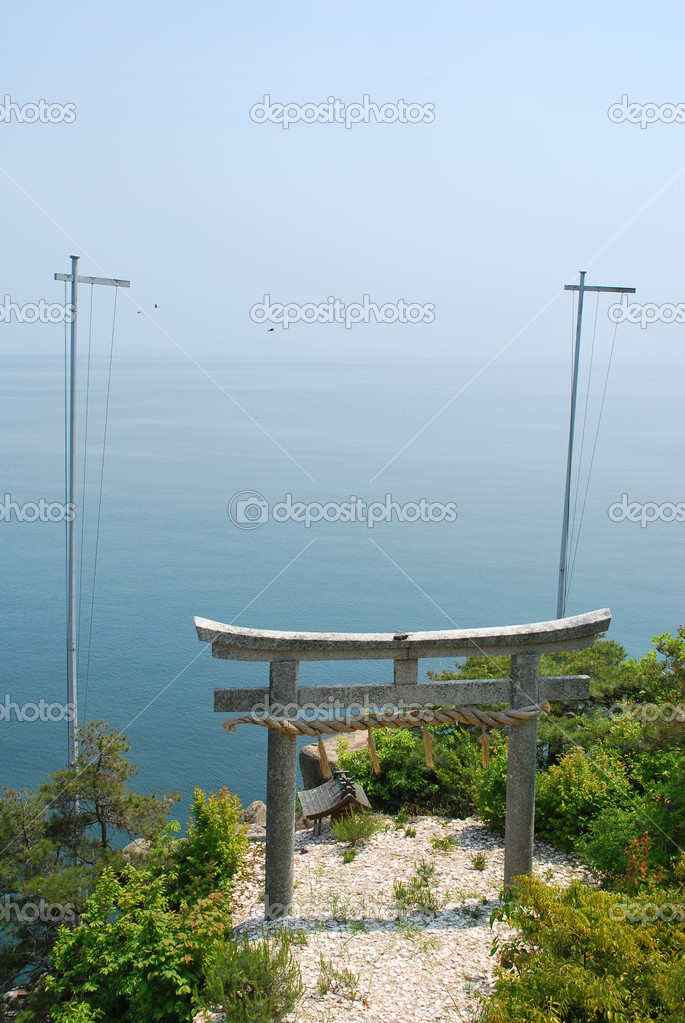 Majestic torii gate of a shrine overlooking the ocean with ships approaching. A symbol of religion, faith, serenity and worship. — Stock Photo #5845242