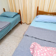 Twin beds in simple motel room — Stock Photo