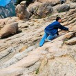 Young man climbing treacherous steep mountain cliff — Foto Stock