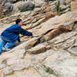 Young man climbing treacherous steep mountain cliff — Stock Photo