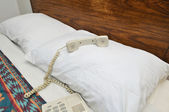 Telephone on bed pillow — Stock fotografie