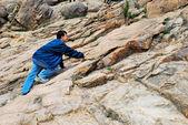 Young man climbing treacherous steep mountain cliff — Stock Photo