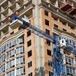 Crane and highrise construction site - Stock Photo