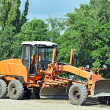 Grader on road construction site - Stock Photo